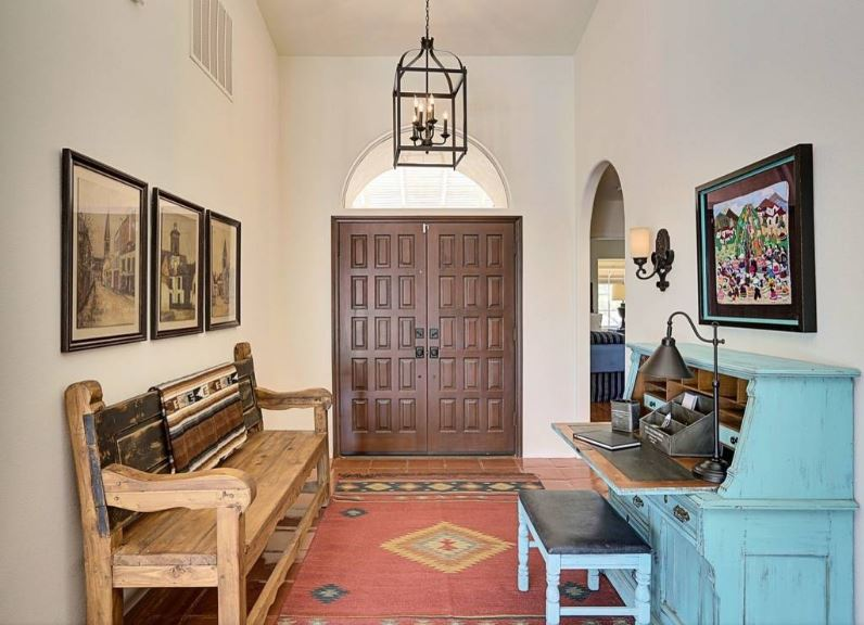 This is a simple and classic Southwestern-style foyer with an elegant dark wooden main door, terracotta flooring tiles that is mostly covered by the red woven area rug and a wooden bench on the side that is adorned with classic photos mounted on the beige wall above it.