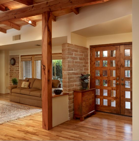 The wooden main door has a checkered pattern on it with small glass panels in the middle. This pairs well with the wooden apothecary drawers on the side by the small brick wall. The rest of the home is dominated by the wooden exposed beams of the ceiling that match the door.