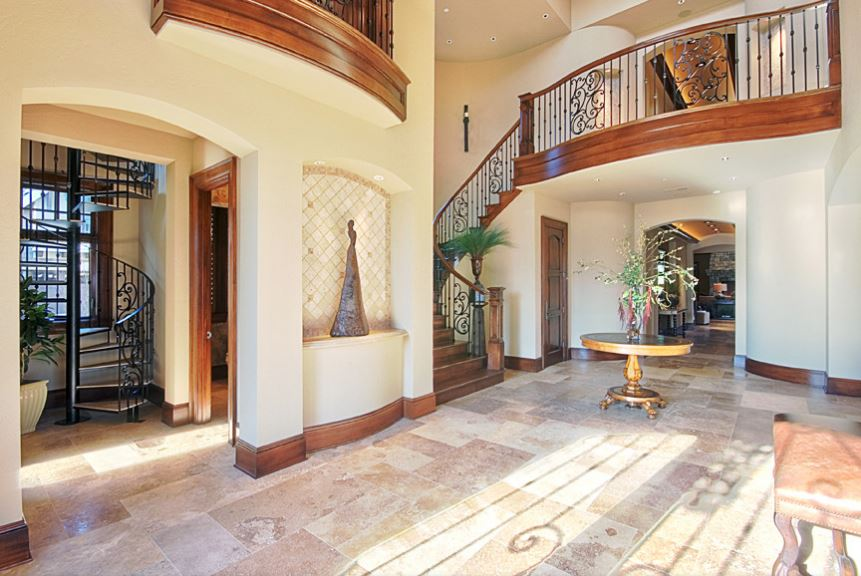 This is a bright and airy grand foyer with a clear view of the second level landing and its wrought iron railings and wooden banisters that match the wooden molding running the beige walls. This is paired with marble flooring that is brightened by the glass panels of the main door.