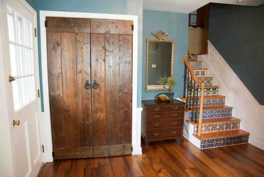 This is a simple foyer that is dominated by the wooden elements of the hardwood flooring, wooden main doors and the wooden drawers beside it that is flanked on the right side by the staircase that has colorful patterned tiles on its steps.