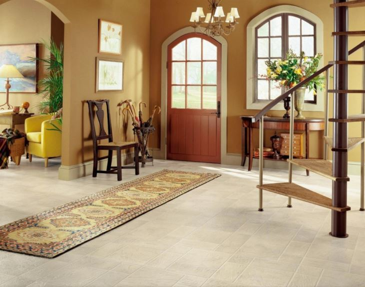 This is a small foyer with white textured flooring that is topped with a narrow colorful patterned area rug. This has a yellowish hue that matches well with the earthy beige walls that complement the arched wooden main door that has glass panels in the middle like the window beside it.