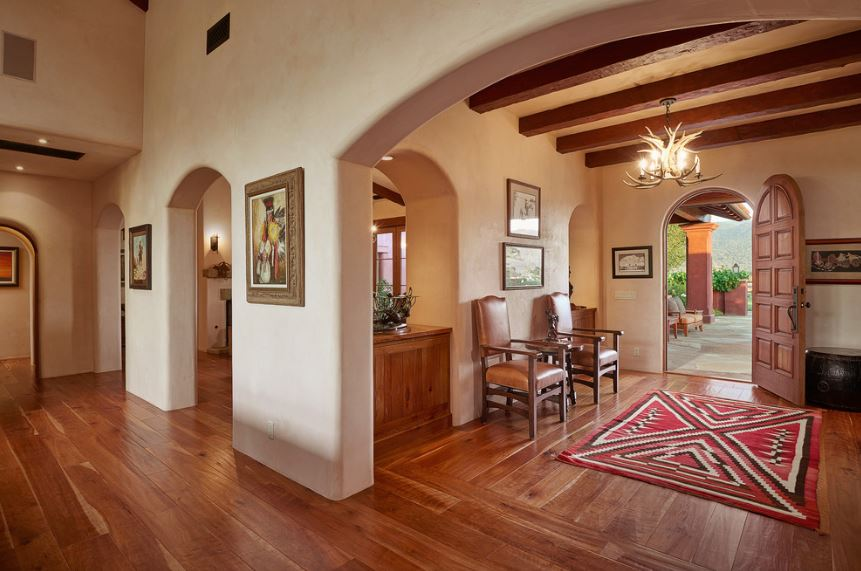 The beige ceiling is dominated by redwood exposed beams that support a decorative antler chandelier over the red patterned area rug over the hardwood flooring. This matches well with the wooden arched main door and brown leather armchairs on the side.