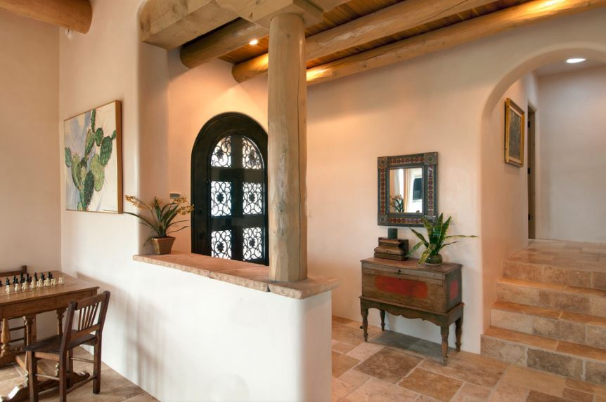 Upon entry of the arched black door that has glass panels, you are welcomed by this simple and small Southwestern-style foyer with beige walls and wooden ceiling filled with exposed log beams matching the log column on the side wall across from the mirror.