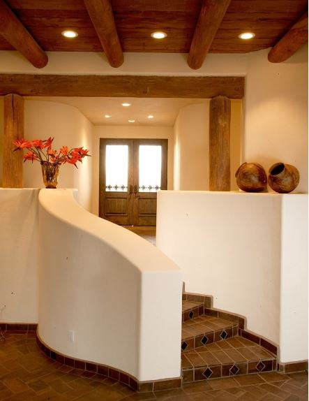 This simple Southwestern-style foyer has brown flooring tiles that complement the wooden log beams on the walls and ceiling. It also matches with the main doors that has glass panels. This leads to a small set of stairs adorned with jars and flowers that stand out against the white structure.