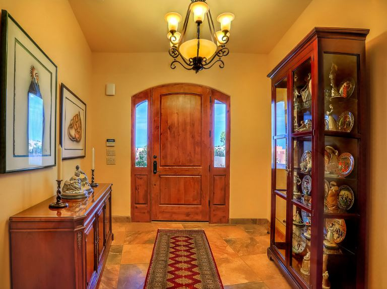 The display cabinet of this Southwestern-style foyer is filled with figurines and ceramic wares. This is paired well to the decors on the console table and the framed artworks on the beige walls that are complemented by the wooden main door.