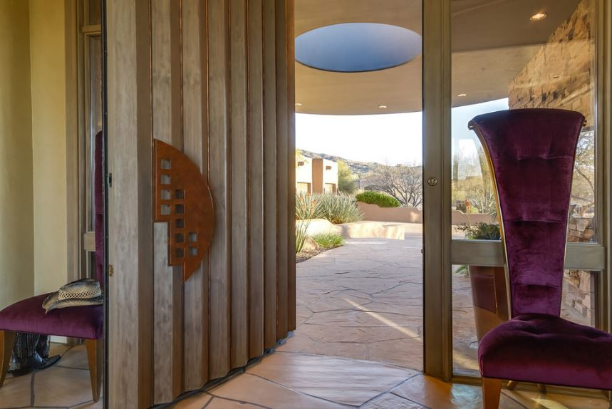 The wooden main door of this Southwestern-style foyer has a design that makes it look like an accordion. This is flanked by two tall and wide glass side lights that are each adorned with a tall and narrow purple velvet cushioned chairs.