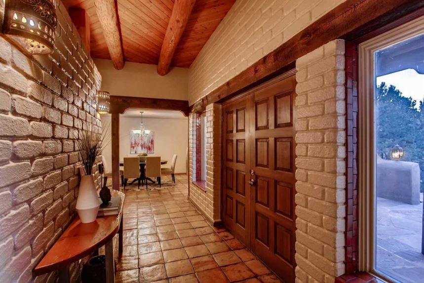This hallway-like foyer has terracotta flooring tiles paired with white brick walls and a wooden arched ceiling that goes well with the wooden main doors. This is flanked by two large glass windows that illuminate the walls together with the wall-mounted lamps.