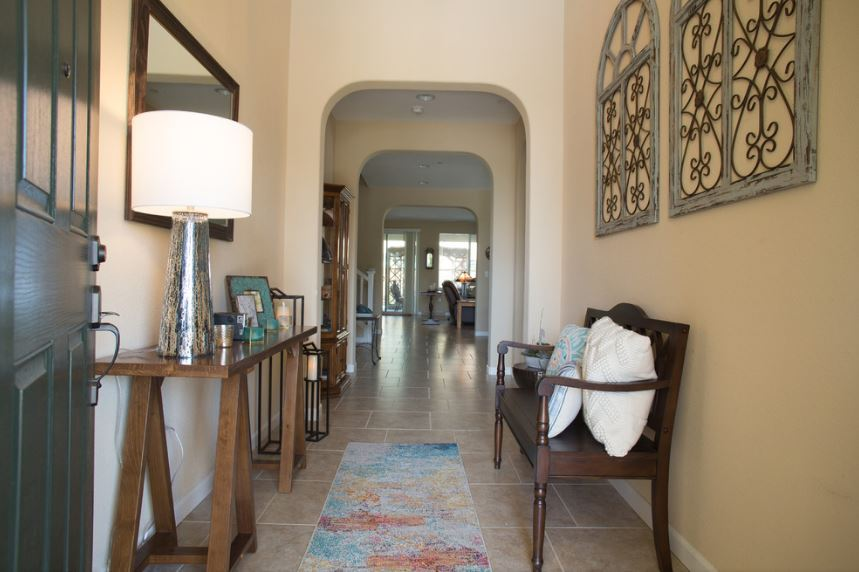 The dark wooden bench that has light hued pillows stands out against the beige walls of this Southwestern-style foyer. This pairs well with the dark wooden console table across from it that bears decors and a lamp as well as a mirror.