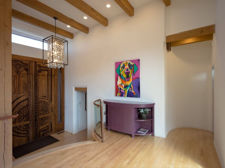 The charming and intricate carvings of the wooden doors share the spot light for attention with the colorful painting of a happy dog. These two elements present a warm welcome for the guests. The white walls match the white ceiling that has exposed wooden beams.