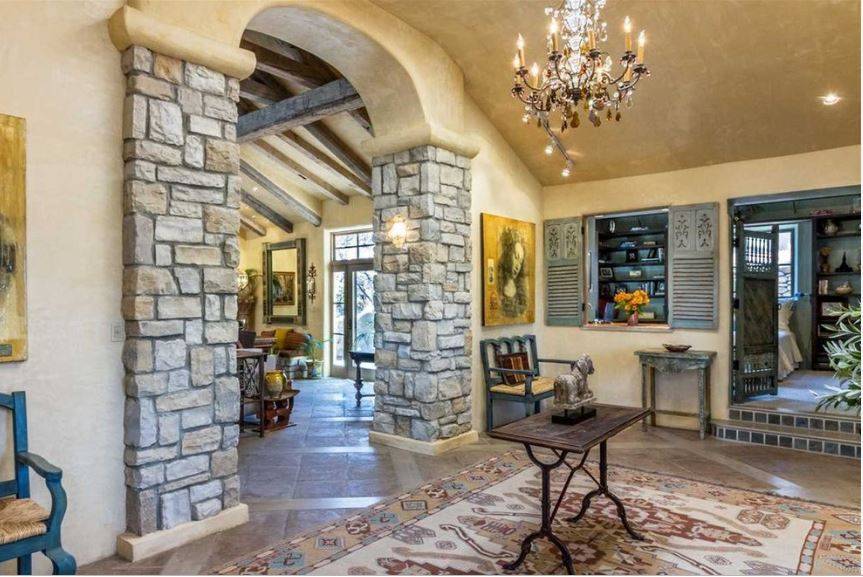 This spacious Southwestern-style foyer has brown marble flooring that is mostly covered by a colorful patterned area rug. This pairs well with the beige walls and cathedral ceiling with a brilliant chandelier that illuminates the blue wooden benches flanking the stone pillars of the arched entryway.
