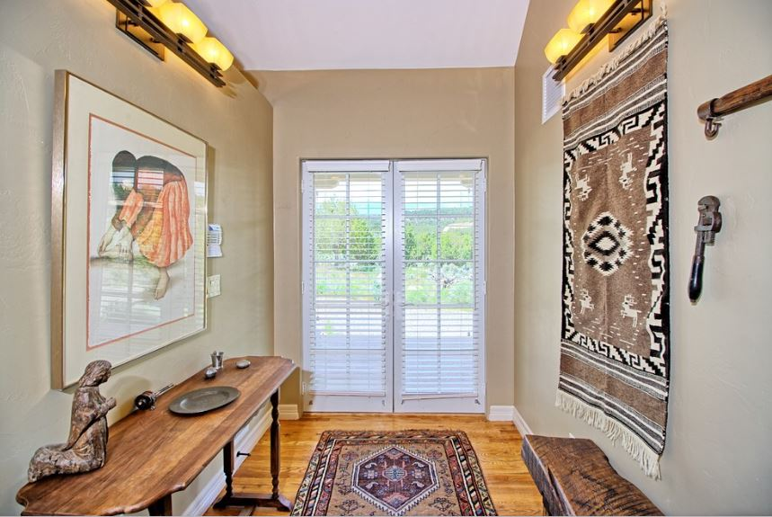 This small and simple hallway-type foyer has beige walls that complement the white molding and white glass doors with blinds. The walls are accented with a colorful patterned tapestry on one side and a colorful framed painting on the other above the wooden console table.