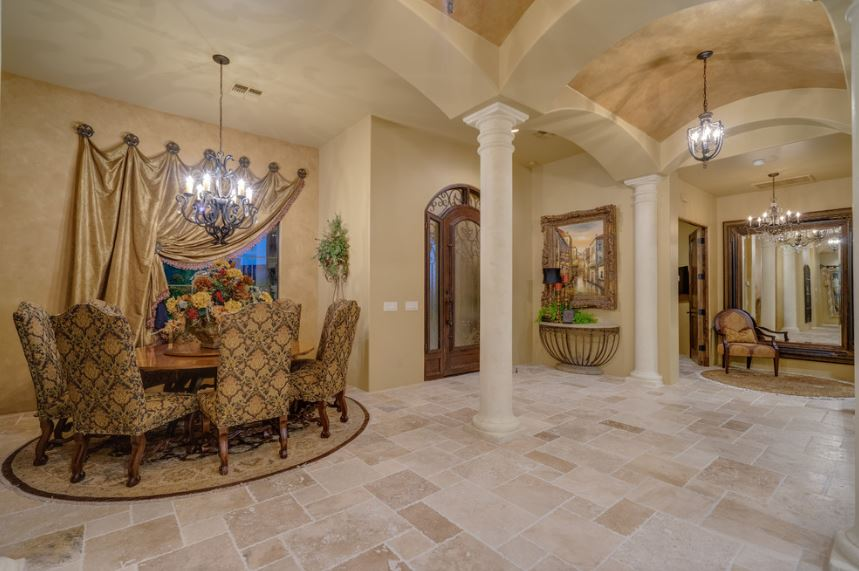 This is a small Southwestern-style foyer right next to the elegant dining area lit with a brilliant wrought iron chandelier that also casts brightness onto the beige marble flooring of the foyer. This flooring matches well with the darker shade of beige on the walls with pillars and a groin arch ceiling.