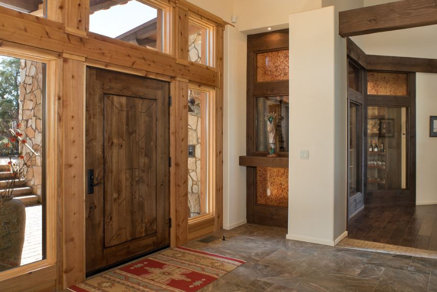 The exterior walls leading to the wooden main door are made of stone that complements the wooden hue of the main door that has tall glass side lights and a row of transom windows that illuminate the light gray walls of this Southwestern-style foyer.