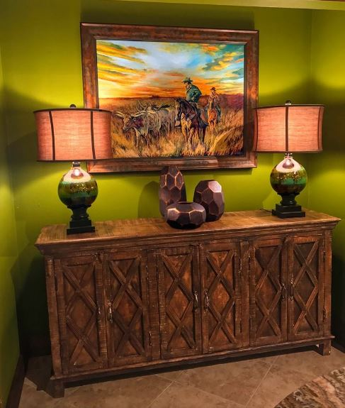 This Southwestern-style foyer has avocado green walls that welcomes its guests with a cheerful demeanor. This green wall is adorned with a wooden cabinet that acts as a console table for the decors and the lamps that illuminate the colorful classic cowboy painting.