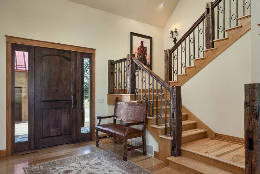 This is a simple and homey Southwestern-style that has a simple wooden main door flanked by glass side lights with frames that match the door and the wooden posts of the stair railings. Beside this is a comfortable wooden chair with a matching dark brown leather cushion.