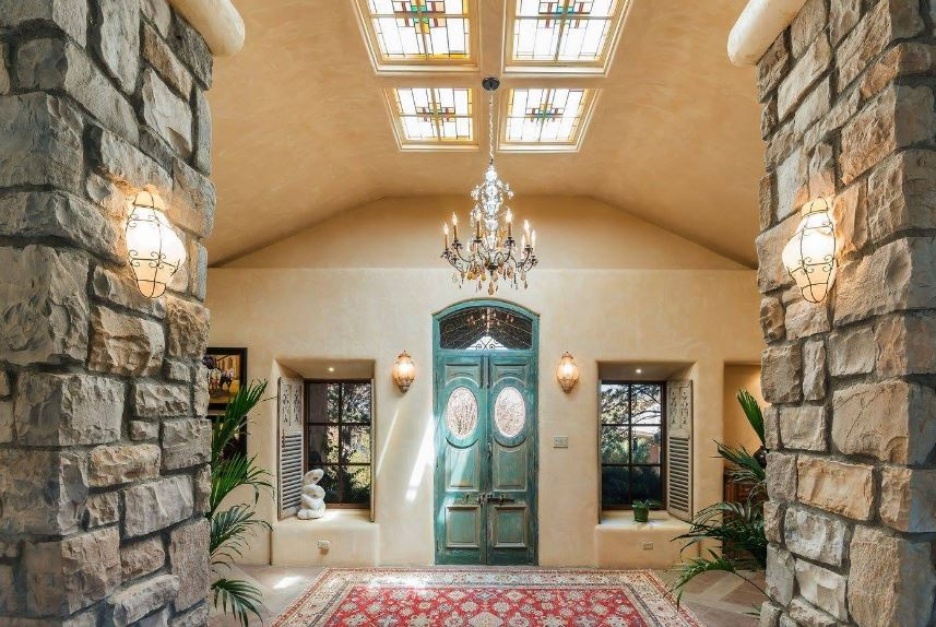Upon entry of the distressed green wooden main doors, you are welcomed by this Southwestern-style foyer with a beige cove ceiling adorned by a set of stained glass sky lights and a majestic chandelier that matches the colorful patterned area rug underneath.