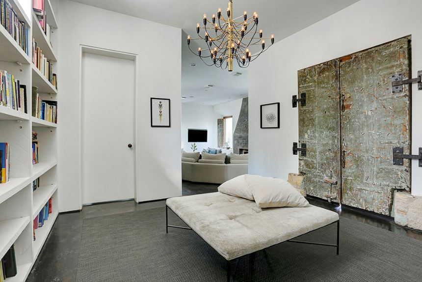 This impressive foyer is inspired by both Southwestern-style and Industrial-style. It has an Industrial-style metal door that stands out against the white walls and ceiling that is dominated by a large intricate chandelier over the cushioned bench in the middle.