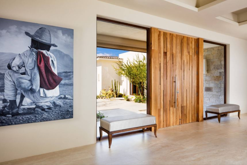 The wooden main door of this bright Southwestern-style foyer stands out with its two wide glass walls that flank it. These are paired with cushioned benches so people wouldn't mistake to walk through it. The highlight of this foyer is the large painting on the side.