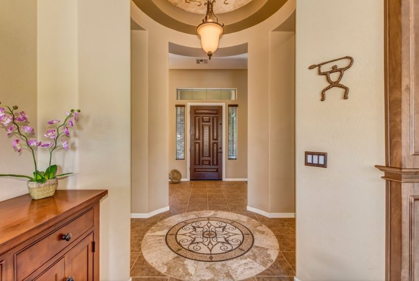 This is a small Southwestern-style foyer with a circular shape that matches with the circular design in the middle of the brown marble tiles. This is complemented by the beige walls illuminated by warm yellow lights of the pendant light.