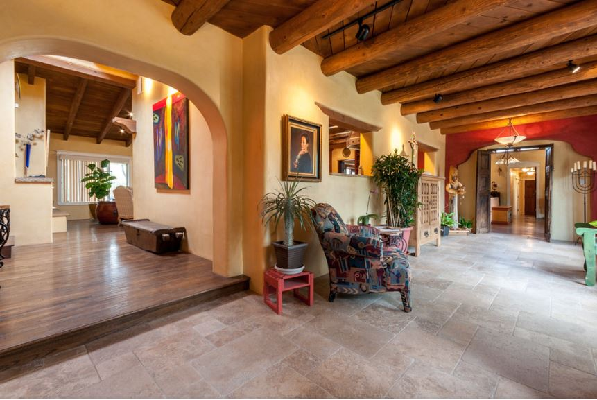 This is a spacious and airy Southwestern-style foyer with a wide wooden ceiling that is dominated by exposed log beams. These complements the yellow walls that are adorned with various painting, decors and even a statue by the corner.