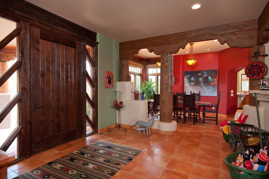 The large wooden main door is paired with side lights that has glass panels that bring in natural lights that brighten the terracotta flooring tiles. This is topped with a colorful patterned area rug and various colorful decorations.