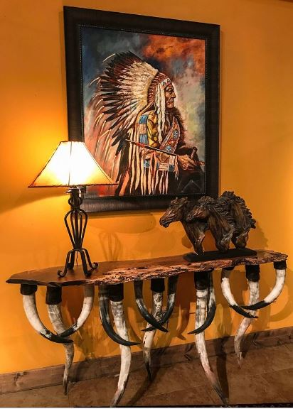This Southwestern-style foyer has a beautiful and unique console table that has legs made of bull horns and a rustic wooden table top. This is augmented with horse figurines as well as a colorful painting of a Native American Indian chief mounted on the mustard yellow wall.