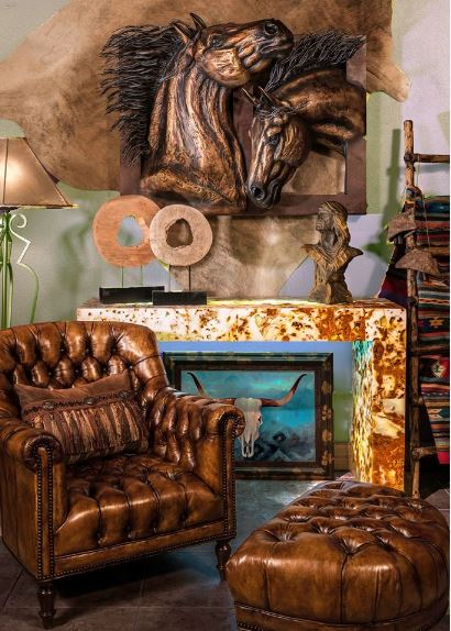 This is a cozy and elegant Southwestern foyer that has a sitting area with a dark brown leather armchair paired with a foot stool of the same hue. This is given a complex background filled with decors like the large embossed horse heads.