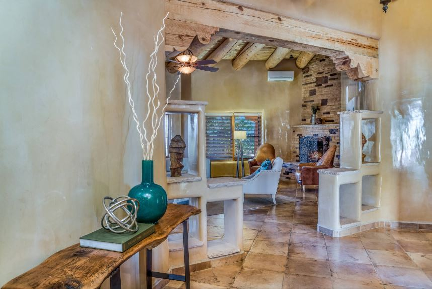 This is a simple foyer in that distinctive Southwestern-style. This foyer has a long console table with a rustic wood top supported by dark iron legs. This is then adorned with a green jar that stands out against the curved gray walls blending with the unique entryway.