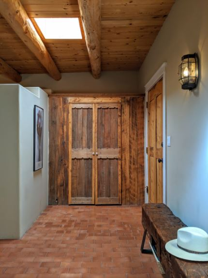 The red brick flooring of this Southwestern-style foyer is a nice complement to the light blue walls that makes the wooden main doors and wooden bench stand out as they are illuminated by the skylight of the wooden ceiling that has exposed wooden log beams.