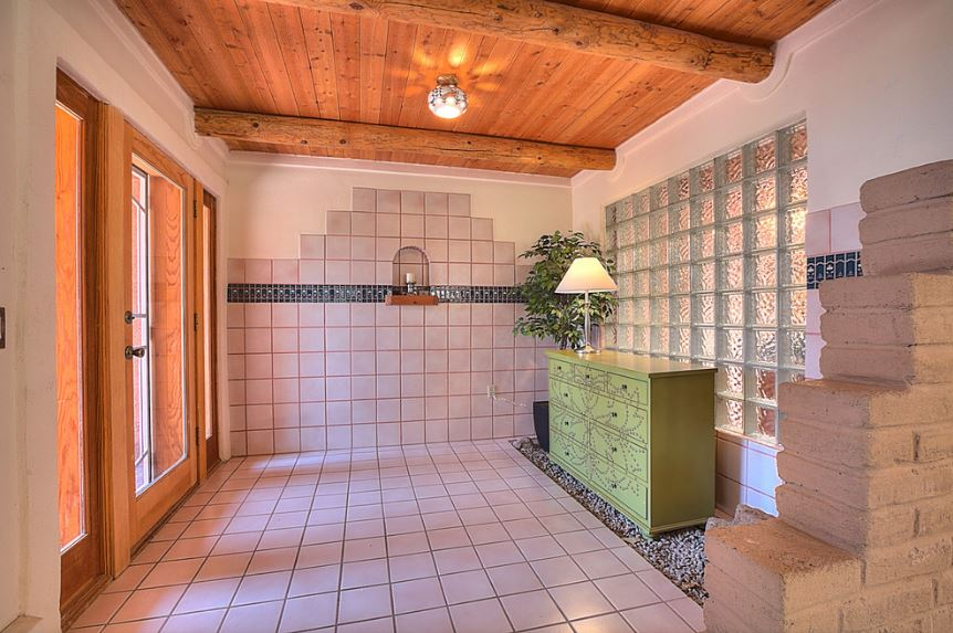 At first glance, this Southwestern-style foyer looks like a bathroom due to its off-white tiles and frosted glass wall behind the green patterned dresser and its potted plant at the corner. This setup is paired with a wooden ceiling that matches with the wooden main door that is dominated by glass panels.