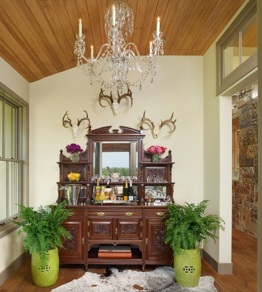 Upon entry of this charming Southwestern-style foyer, you will be welcomed by the elaborate setup against the white wall that makes the brown cabinet stand out. This is accented with small horned-animal skull decorations along with various decors that match with the crystal chandelier.