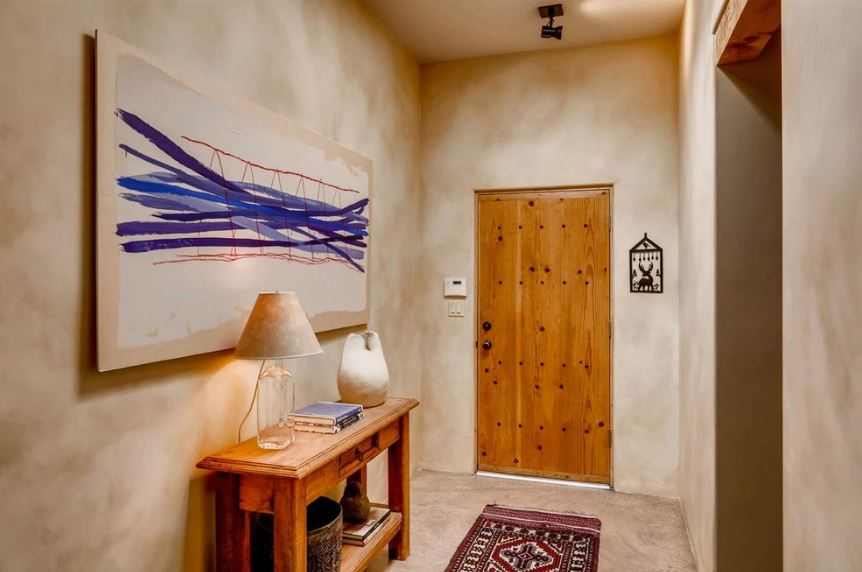This is a simple and welcoming Southwestern-style foyer with a wooden main door that matches the tone of the wooden console table on the side that stands out against the cloudy gray walls. This matches with the flooring adorned with a colorful patterned area rug.