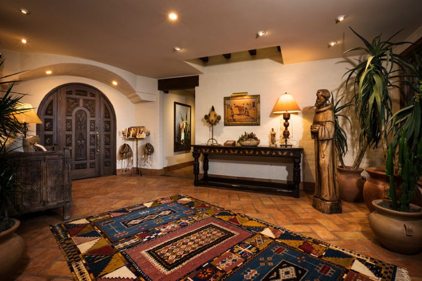 The beautiful terracotta flooring tiles of this Southwestern-style foyer is accented with a colorful patterned area rug. This brings in a dash of color to the earthy tones of the dark wooden arched main door that matches with the wooden console table that has a statue beside it along with potted plants.