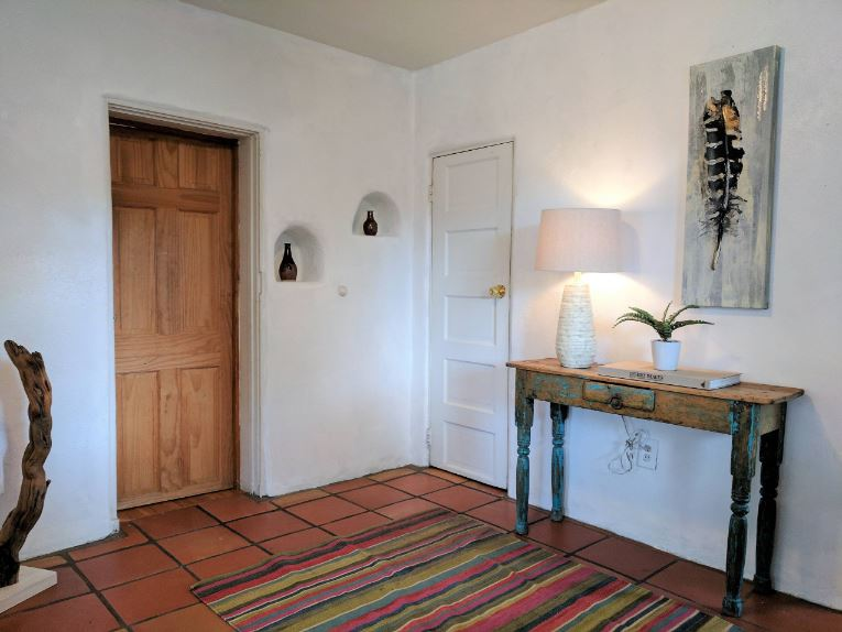 The stark white walls of this Southwestern-style foyer is beautifully contrasted by the earthy terracotta flooring tiles and its colorful patterned area rug. This works well with the distressed rustic wooden console table topped with a table lamp and a colorful painting.