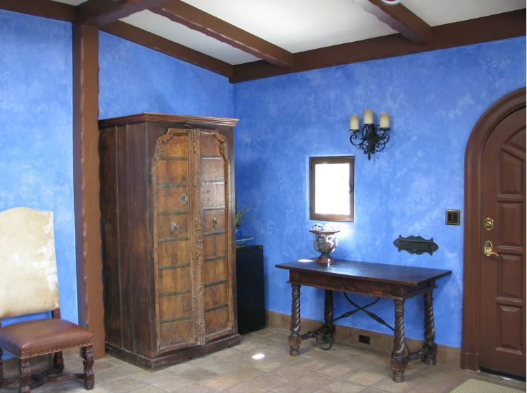 The cheerful blue walls are a nice bright contrast for the dark wooden elements of the arched wooden door, console table, cabinet and the chair beside it that has a dark brown leather seat cushion. These are paired well with the dark brown beams of the white ceiling.