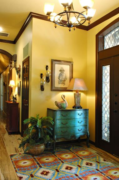 Upon entry of the main doors that have patterned stained glass panels, the guests are cheerfully met by the colorful patterned area rug with a woven quality to it. This is paired with a distressed green wooden drawer that goes well with the yellow walls. This is enhanced by the yellow lights of the chandelier above.