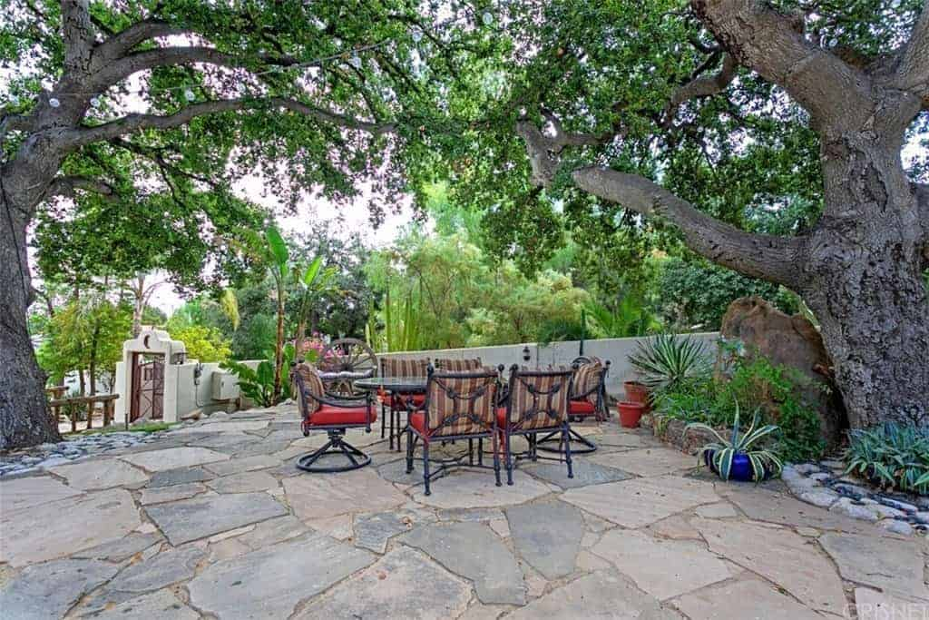 This is a relaxing backyard with a couple of large Ancient-looking trees that provide a wide canopy of leaves and branches over the outdoor dining area on the mosaic rock flooring surrounded by various shrubs and potted plants that contrast the red cushions of the dining chairs.