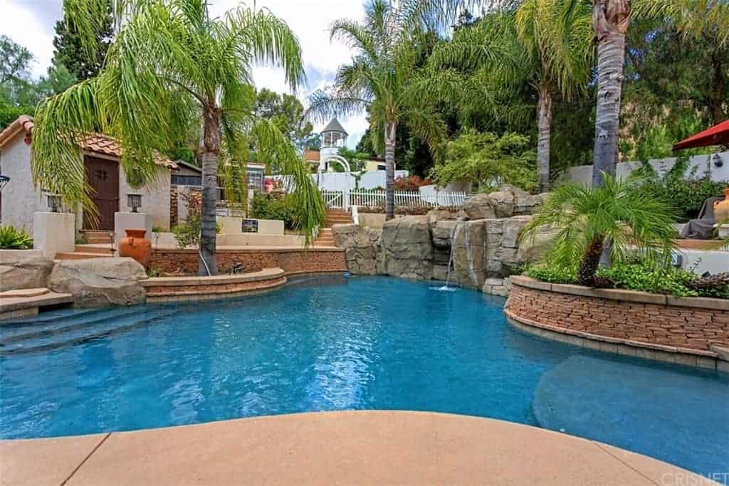 This Southwestern-style landscaping boasts of a beautiful curved pool adorned with various tall tropical trees placed in strategic spots to complement the large rock structure that serves as a miniature waterfalls for the blue pool that is contrasted by the red brick planters.