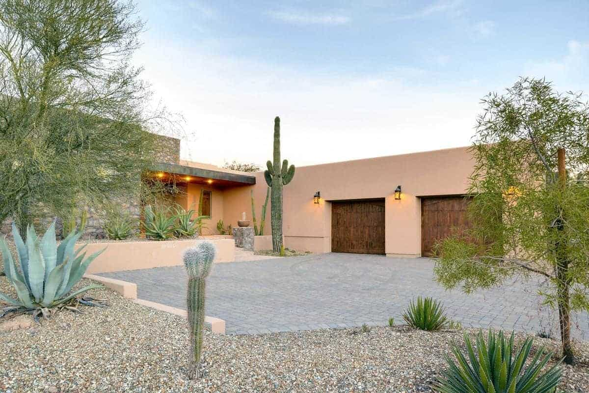 This is the spacious courtyard and driveway in front of the house that has beige walls complemented by this Southwestern-style landscaping. The concrete gray driveway is surrounded by graveled area planted with various cacti and succulents with a highlight of a very tall cacti by the entryway.