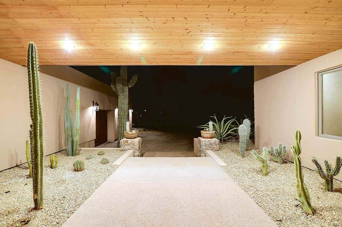 This is distinctly an example of Southwestern-style landscaping. This is the entryway near the main door with a concrete walkway that is flanked by graveled plots of soil planted with different cacti and succulents that are illuminated by the recessed lights.