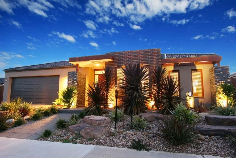 This is the front view of this lovely home bathed in warm and welcoming yellow lights that also gives accent to the Southwestern-style landscaping filled with decorative rocks and stones in between shrubs and plants that have a dramatic look against the yellow light.