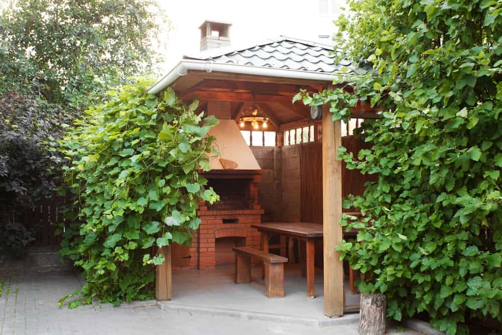 There is a small structure like a gazebo built inside the grounds of this home that has an outdoor dining area of wooden table and benches warmed by the fireplace that is mostly made of red bricks complete with a brick stone chimney jutting out of the roof that is adorned by the tall shrubs.