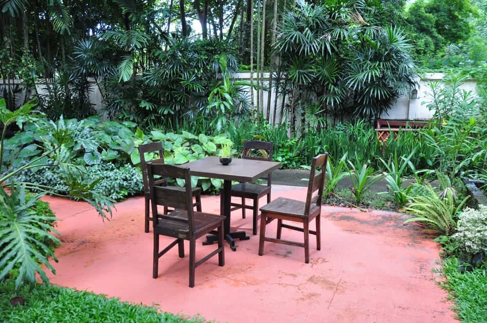This outdoor dining area has a small square wooden table paired with four wooden chairs with a dark wooden tone that stands out against the terracotta flooring that is surrounded by ferns and flowering plants as well as tall trees with large tropical leaves.