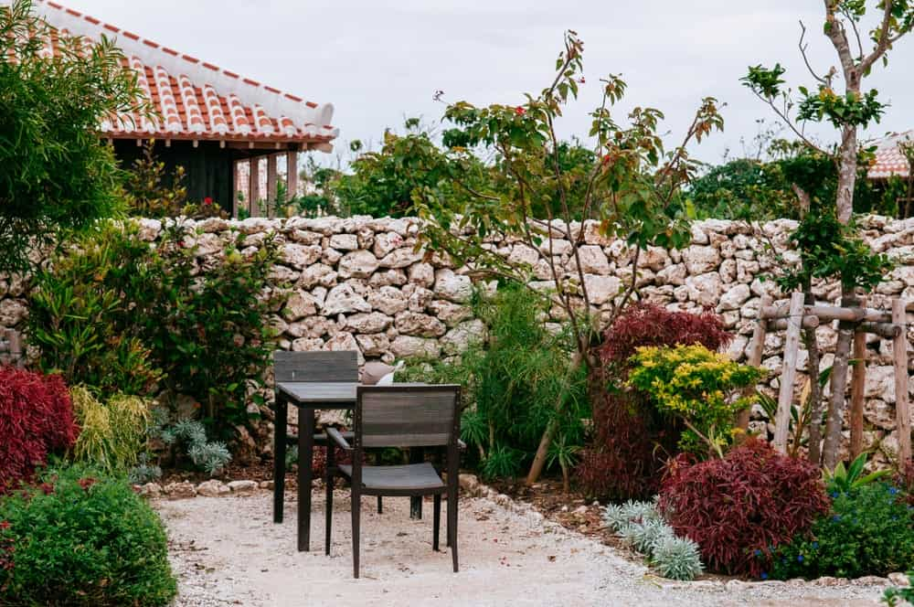 This is a cozy and charming sitting area that can double as an outdoor dining area. It has a square wooden table paired with a couple of wooden plank armchairs. These stand out against the sandy flooring and walkway adorned with the surrounding colorful shrubs.
