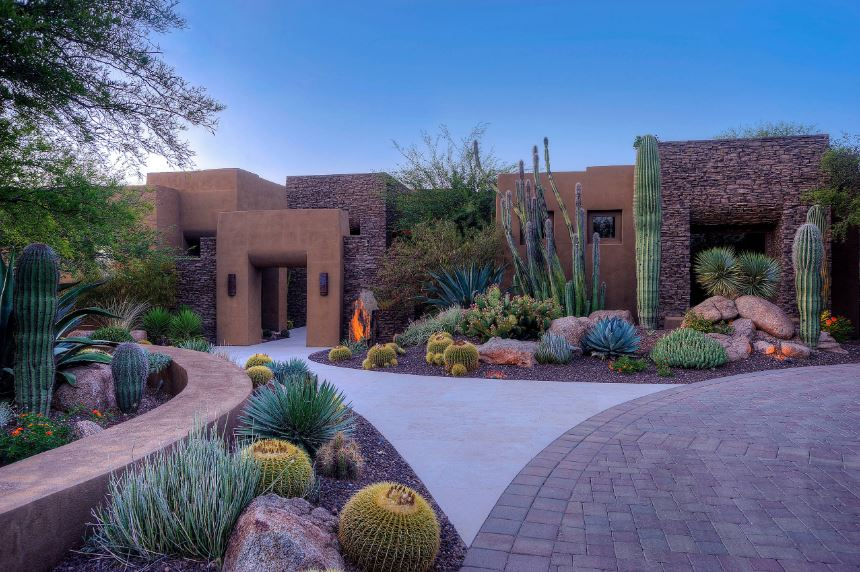 The earthy tone of the exterior walls of this home is augmented by the stone walls that match the pebbled soil of the Southwestern-style landscaping that is filled with various cacti and large succulents bringing splashes of color along with decorative rocks.