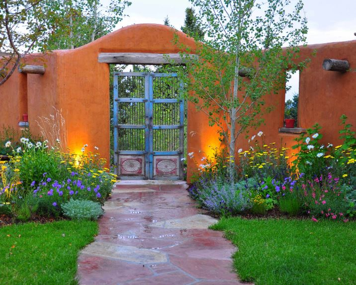 A charming earthy orange tone is applied to the stone walls of the fence that pairs well with the distressed blue wooden gate. This is further elevated by the colorful flowers of the surrounding shrubs and grass that flank the mosaic terracotta walkway.