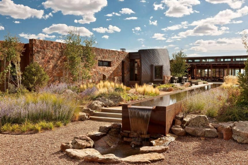 The brilliant blue sky is a perfect contrast to the earthy palette of this Southwestern-style landscape that seem to match the stone walls. This is also augmented by the man-made stream that runs alongside the stone walkway leading to the entryway of the home.