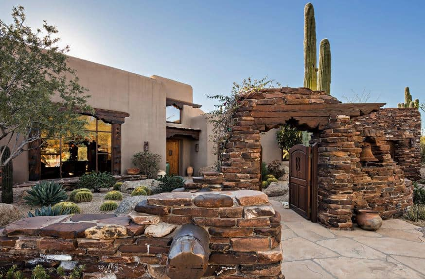 This Southwestern-style landscaping is intentionally made to look like a ruin of a large stone structure. This gives the simple gray exteriors of the house a charming character augmented by the green hue of the various cacti and succulents planted on pebbled grounds.