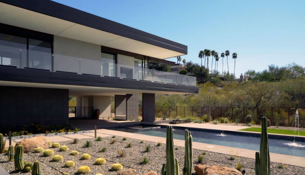 This is a neat and clean application of the Southwestern-style landscaping that matches well with the modern lines and angles of the home. The various cacti and succulents are planted in perfect measured sequence on the side of the rectangular swimming pool of the backyard.
