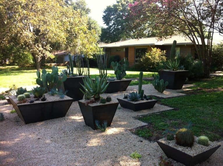 This is a classic and traditional home with a matching landscaping. This is adorned by the Southwestern-style landscaping applied to a corner of the property. The carpet of grass were replaced by sand and pebbles that contrast the large dark planters that bear various small cacti and succulents.